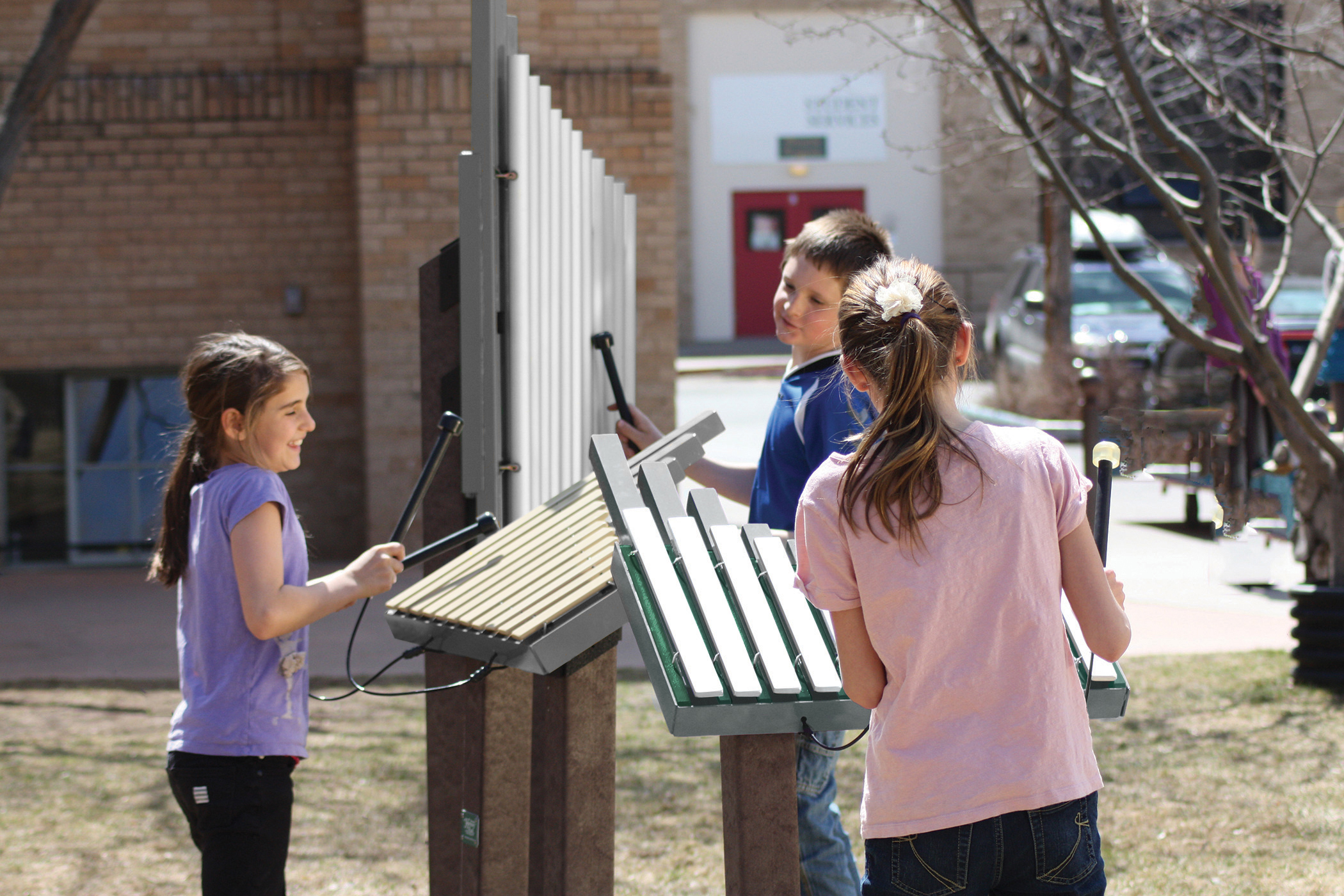 Children playing on outdoor musical instruments