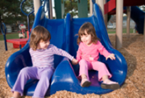 children sliding down a double-slide